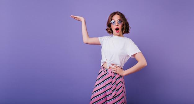 Chica elegante con cabello castaño ondulado que expresa emociones de sorpresa durante la sesión de fotos. retrato de interior de mujer caucásica sorprendida en vasos de pie en la pared púrpura con la mano hacia arriba