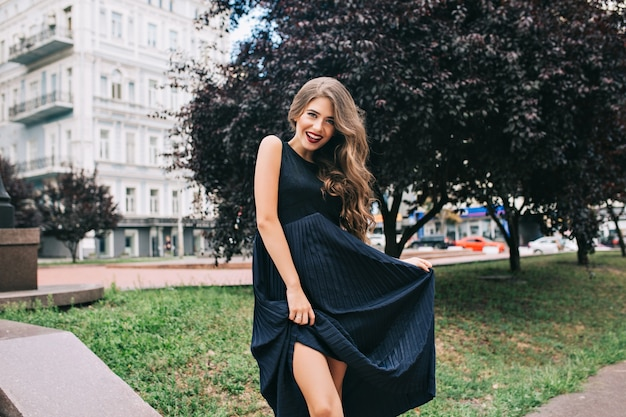 Chica elegante con cabello largo y labios vinosos está posando en el parque ciyu.