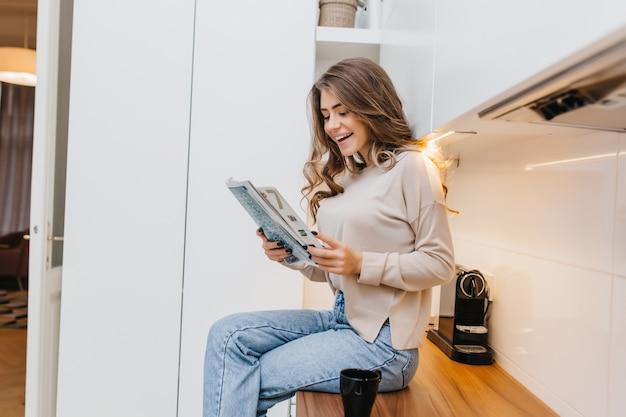 Chica elegante con cabello largo sentado con las piernas cruzadas en la cocina y leyendo noticias con una sonrisa
