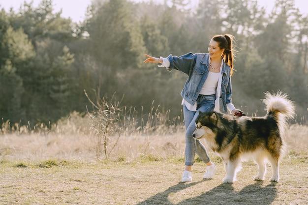 Chica elegante en un campo soleado con un perro