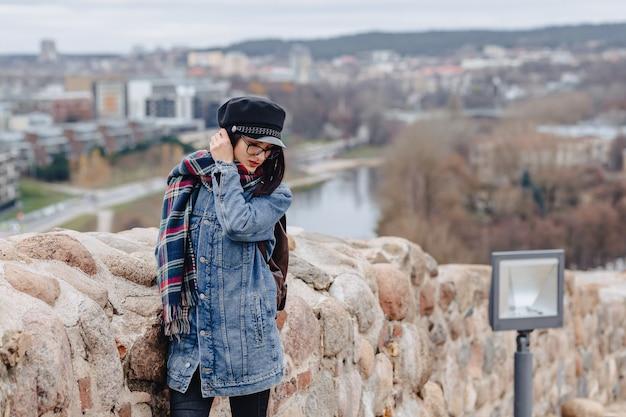 Chica elegante con chaqueta de jeans a pie en el fondo de vilnius