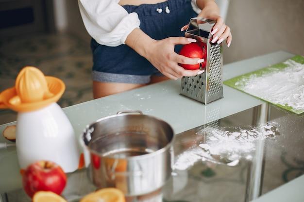 Chica elegante en una cocina con frutas.