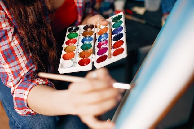 Chica elegante dibuja en un estudio de arte.