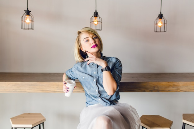Chica elegante de ensueño con cabello rubio y labios rosados, sentada en una cafetería con mesa y sillas de madera. ella sostiene una taza de café
