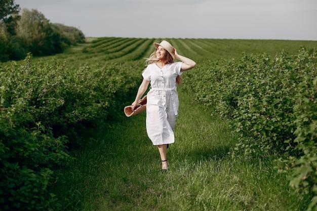 Chica elegante y con estilo en un campo de verano