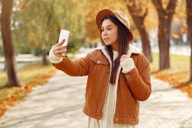 Chica elegante y con estilo en un parque de otoño
