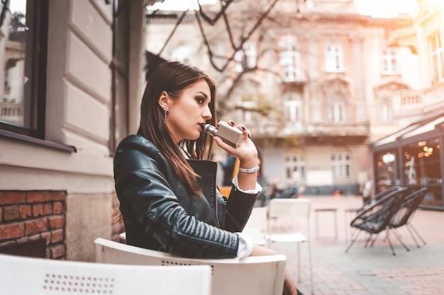 Chica elegante fuma un cigarrillo electrónico.