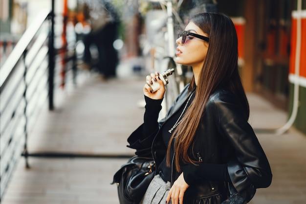 Chica elegante fumando un cigarrillo electrónico mientras camina por la ciudad