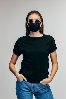Chica elegante con gafas y máscara con camiseta negra posando en la pared gris