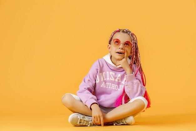 Chica elegante en gafas redondeadas con rastas rosa sentado th