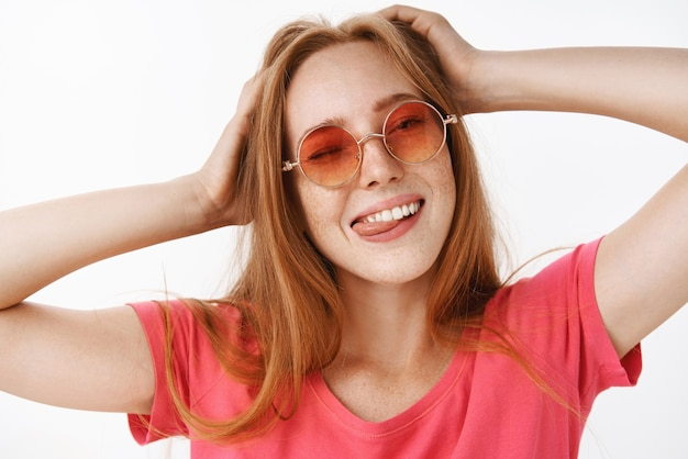 Chica elegante con gafas de sol de moda y camiseta rosa cogidos de la mano en la cabeza guiñando un ojo, sacando la lengua felizmente y sonriendo de alegría y emociones relajadas divirtiéndose, relajándose sobre una pared gris