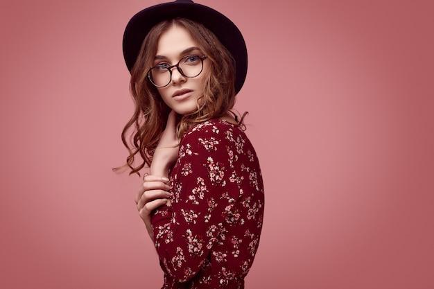 Chica elegante glamour hipster en vestido rojo de moda, sombrero negro y gafas