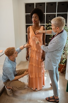 Chica elegante con grandes pendientes y un elegante vestido naranja mientras sonríe y mira hacia otro lado