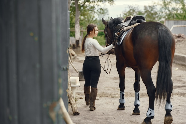 Chica elegante en una granja con un caballo