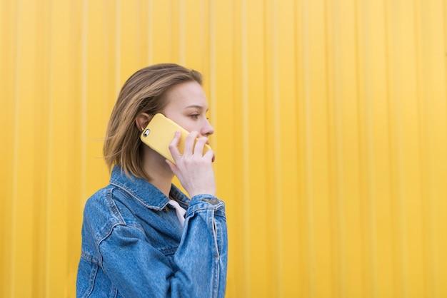 Chica elegante habla por teléfono amarillo sobre fondo de pared amarilla y mira hacia el lado. comunicación por teléfono