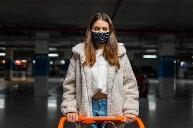 Chica elegante en máscara médica con carrito de compras