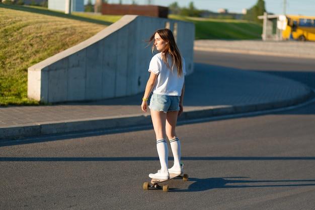 Chica elegante con medias blancas disfruta del paseo en longboard, levanta las manos