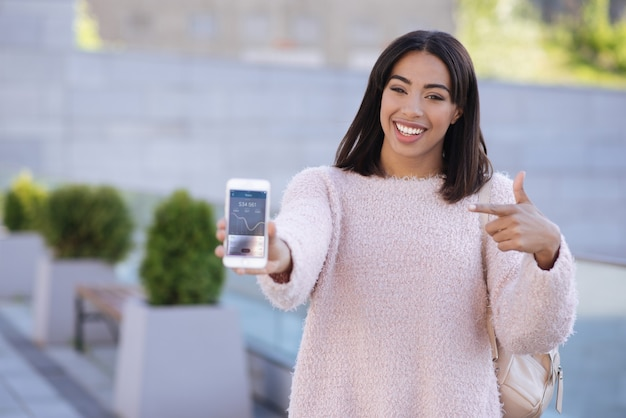 Chica elegante y moderna que le da un consejo a su amigo y muestra cómo se ve la aplicación