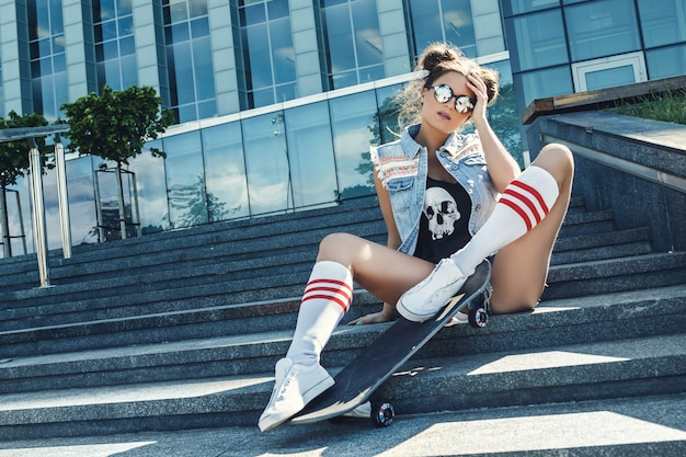 Chica elegante con una patineta en la calle
