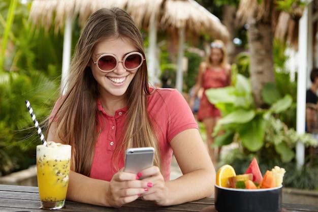Chica elegante con el pelo largo enviar mensajes a amigos a través de las redes sociales en su teléfono celular