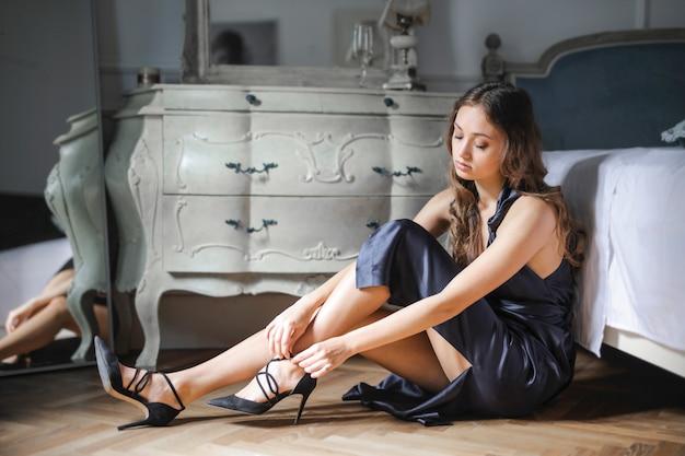Chica elegante poniéndose los zapatos