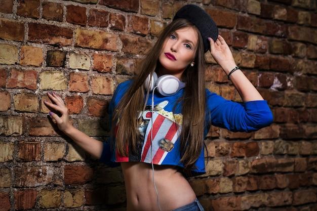 Chica elegante posando cerca de una pared de ladrillos