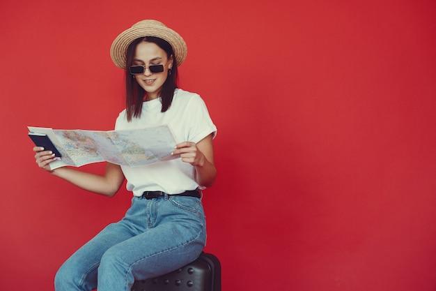 Chica elegante posando con equipo de viaje en una pared roja
