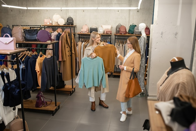 Chica elegante que consulta con su madre mientras elige un nuevo suéter para la primavera en el departamento de ropa de moda durante las compras