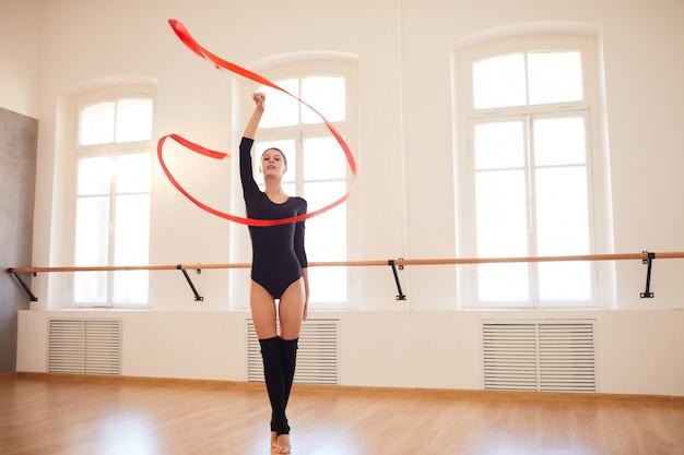 Chica elegante realizando gimnasia rítmica en estudio
