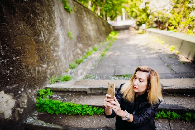 La chica elegante sentada en las escaleras y manteniendo un teléfono móvil