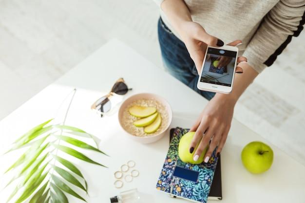 Chica elegante tomando fotos con manzana, cuaderno en la mesa de whie.