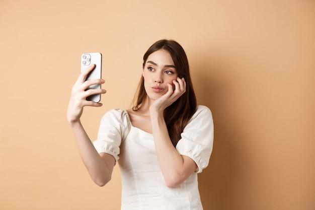 Chica elegante tomando selfie, posando para cámara móvil con filtros de fotos, haciendo cara linda, de pie sobre fondo beige.