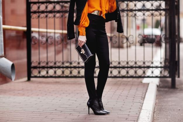 Una chica elegante con un traje negro y una blusa naranja se encuentra cerca de la cerca