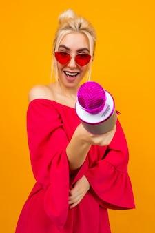 Chica en un elegante vestido rojo con hombros desnudos con gafas retro le ofrece un micrófono al espectador