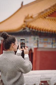Chica elegante visitando la ciudad prohibida en beijing, china