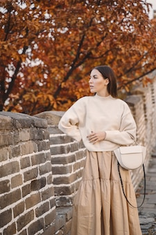Chica elegante visitando la gran muralla china cerca de beijing durante el otoño