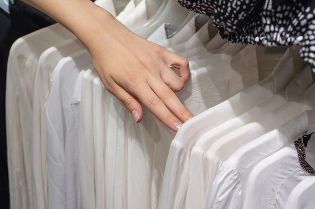 Chica elige una camisa blanca en la tienda. selección de primer plano de las manos de ropa nueva.