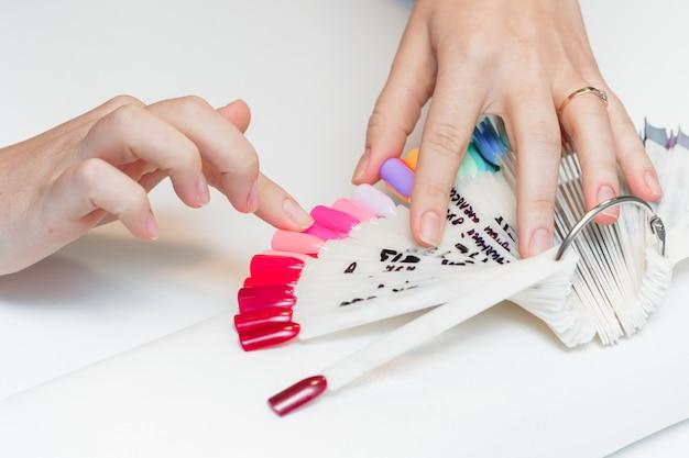 La chica elige el color del polaco para la manicura. probadores de esmalte de uñas