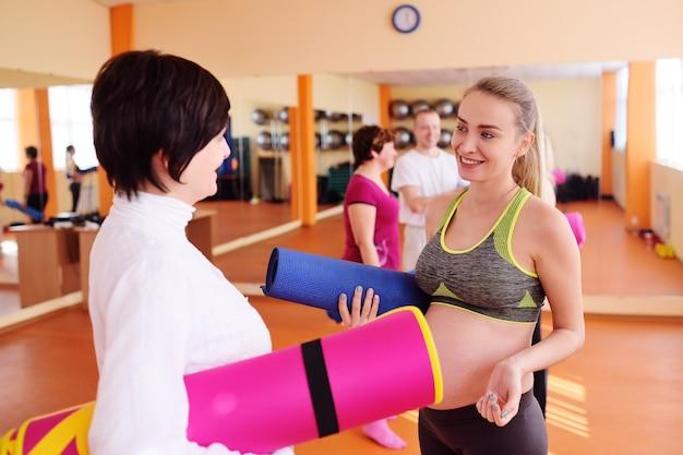 Chica embarazada dedicada a hacer ejercicio junto con un grupo de yoga en un club deportivo