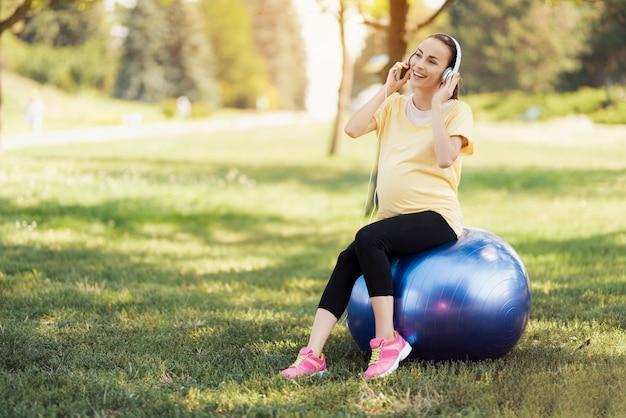 Chica embarazada sonríe y escucha música en el parque.