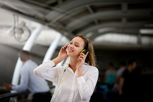 Chica emocionada bailando y escuchando música con auriculares en la calle con felicidad