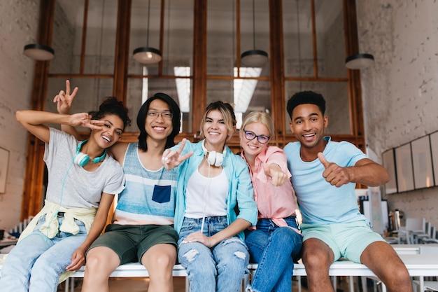 Chica emocionada con camisa azul mostrando el signo de la paz disfrutando de la compañía de un amigo en buen día. retrato interior de estudiantes internacionales felices jugando con fotos y riendo.