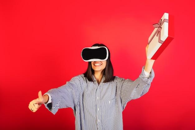 Chica emocionada feliz positiva en gafas de realidad virtual vr con caja de regalo, sonriendo con alegría y mostrando un gesto genial