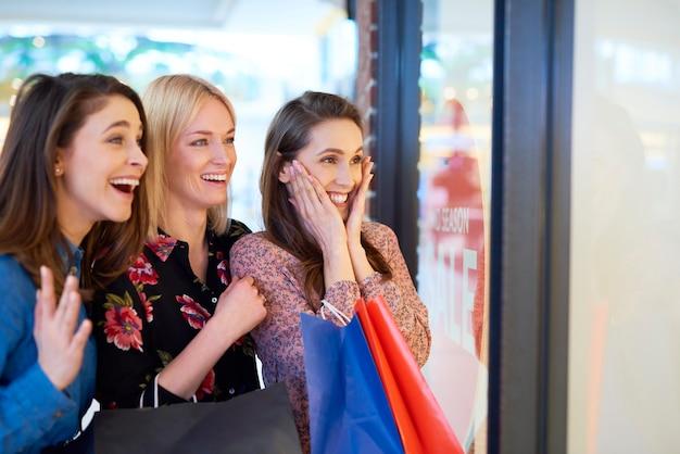 Chica emocionada mirando el escaparate durante las grandes compras