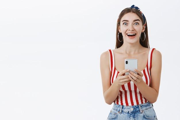 Chica emocionada recibiendo noticias increíbles a través de teléfono inteligente mirando sin palabras de felicidad y emoción no puede creer que tenga tanta suerte sosteniendo el teléfono en las manos sonriendo ampliamente