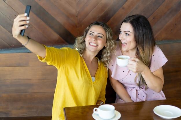 Chica emocionada tomando fotos con su mejor amiga en el café