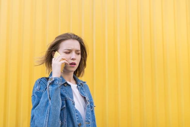 Una chica emocional en chaqueta vaquera habla por teléfono sobre fondo de pared amarilla.