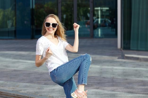 Chica emocional positiva feliz fuera del edificio en verano
