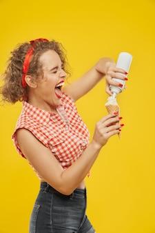 Chica emocional relleno de cuerno de galleta con crema batida.