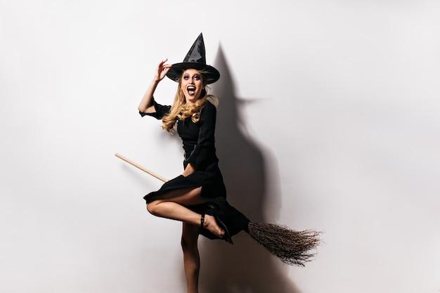 Chica emocional en traje de carnaval expresando felicidad en halloween. encantadora dama rubia lleva sombrero mágico.
